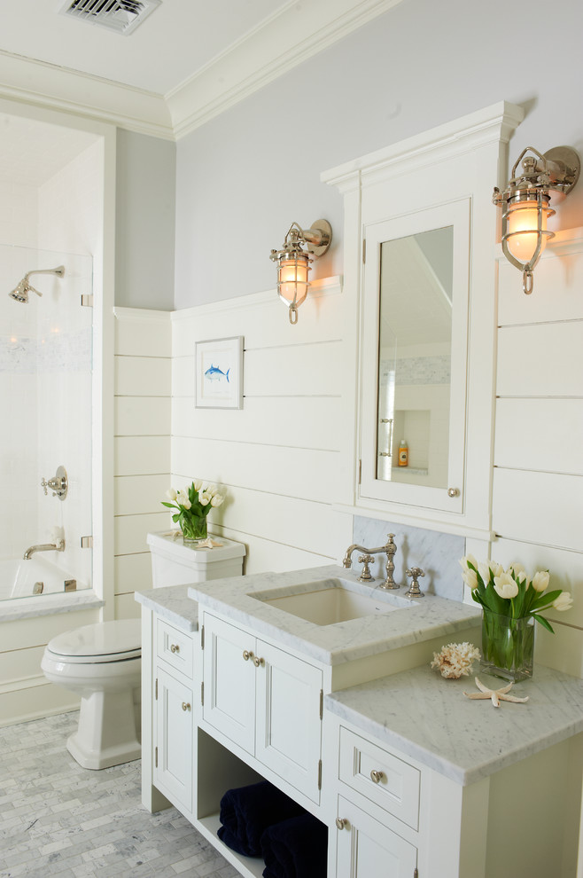 Example of a beach style bathroom design in New York with recessed-panel cabinets, white cabinets, white walls and an undermount sink