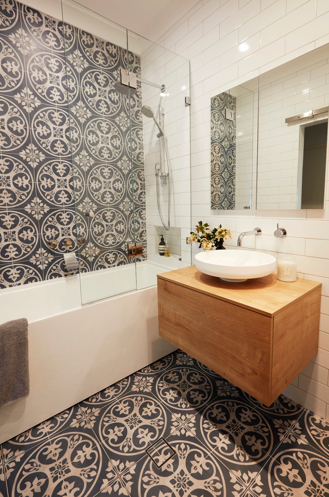 This is an example of a small contemporary master bathroom in Sydney with medium wood cabinets, a freestanding tub, a shower/bathtub combo, a wall-mount toilet, blue tile, ceramic tile, white walls, ceramic floors, a vessel sink and wood benchtops.