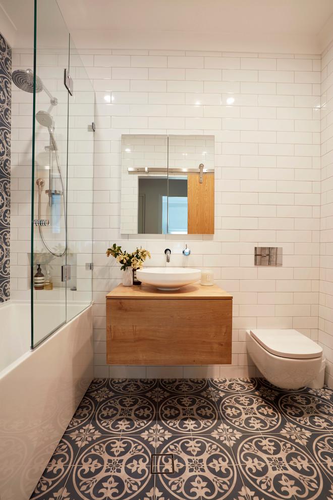 Imagen de cuarto de baño principal, actual, pequeño, con puertas de armario de madera oscura, combinación de ducha y bañera, sanitario de pared, baldosas y/o azulejos azules, baldosas y/o azulejos blancos, paredes blancas, suelo de baldosas de cerámica, lavabo sobreencimera, encimera de madera, armarios con paneles lisos, bañera empotrada, ducha abierta y encimeras marrones