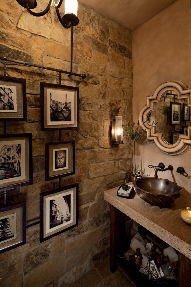 Example of a mid-sized tuscan 3/4 brown tile and stone tile travertine floor bathroom design in Orange County with furniture-like cabinets, distressed cabinets, a two-piece toilet, beige walls, a vessel sink and solid surface countertops