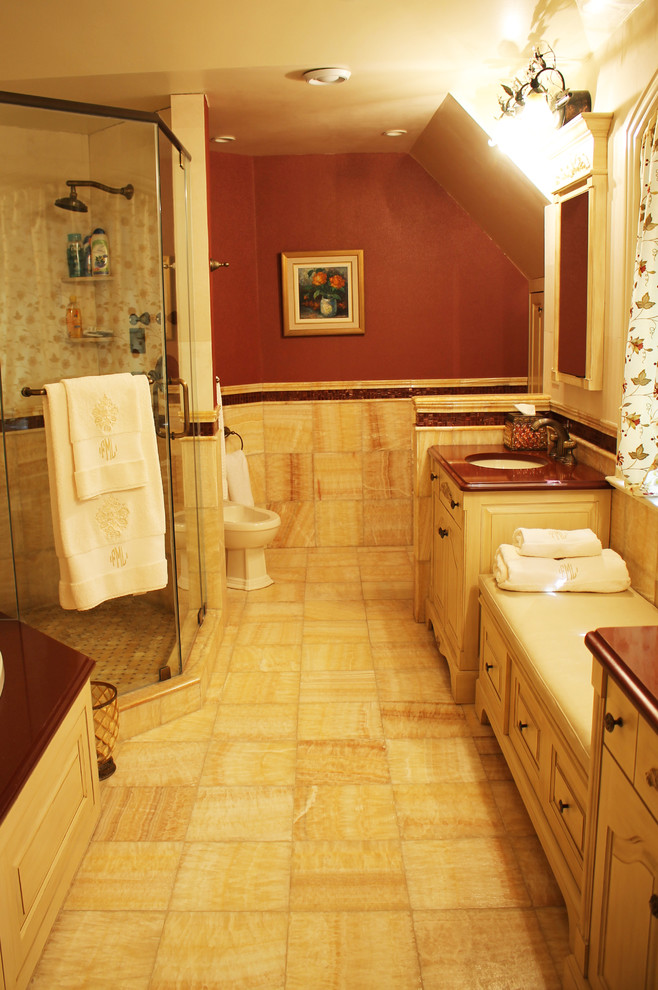 Example of a large tuscan master stone tile and brown tile porcelain tile bathroom design in New York with shaker cabinets, a two-piece toilet, beige walls, a console sink, brown cabinets and marble countertops