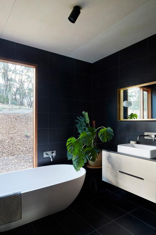 Black wall and floor bathroom with bath near window