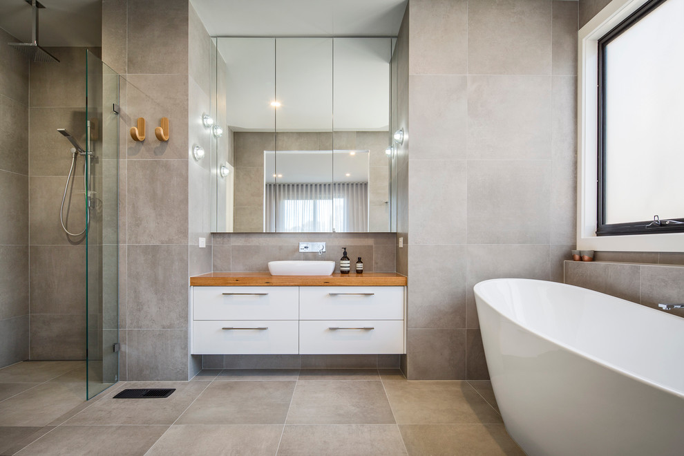 Trendy gray tile bathroom photo in Melbourne with flat-panel cabinets, white cabinets, gray walls, a vessel sink, wood countertops and brown countertops
