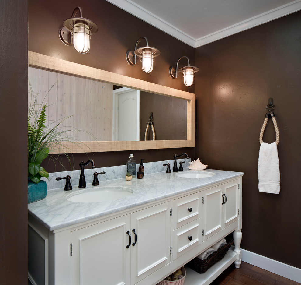 Inspiration for a mid-sized coastal master medium tone wood floor bathroom remodel in San Francisco with an undermount sink, white cabinets, brown walls, a two-piece toilet, marble countertops and recessed-panel cabinets