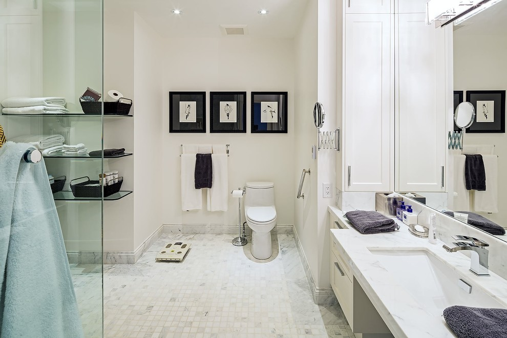 Bathroom - large transitional master white tile and cement tile ceramic tile bathroom idea in Toronto with an undermount sink, white cabinets, a one-piece toilet, white walls, recessed-panel cabinets, marble countertops and white countertops