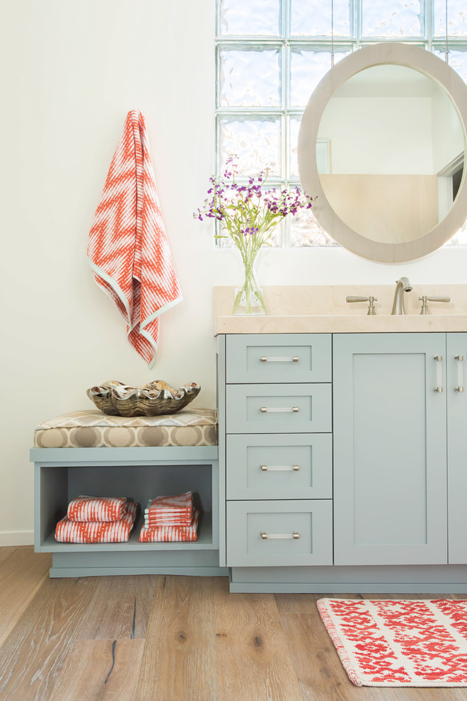 Alcove shower - large coastal kids' beige tile and marble tile light wood floor and gray floor alcove shower idea in Los Angeles with shaker cabinets, blue cabinets, a one-piece toilet, white walls, an undermount sink, marble countertops and a hinged shower door