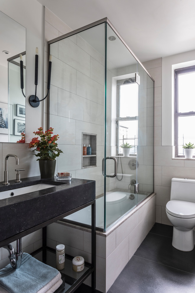 Small transitional 3/4 beige tile and marble tile black floor and ceramic tile bathroom photo in Denver with open cabinets, black cabinets, a one-piece toilet, beige walls, an undermount sink, a hinged shower door and granite countertops