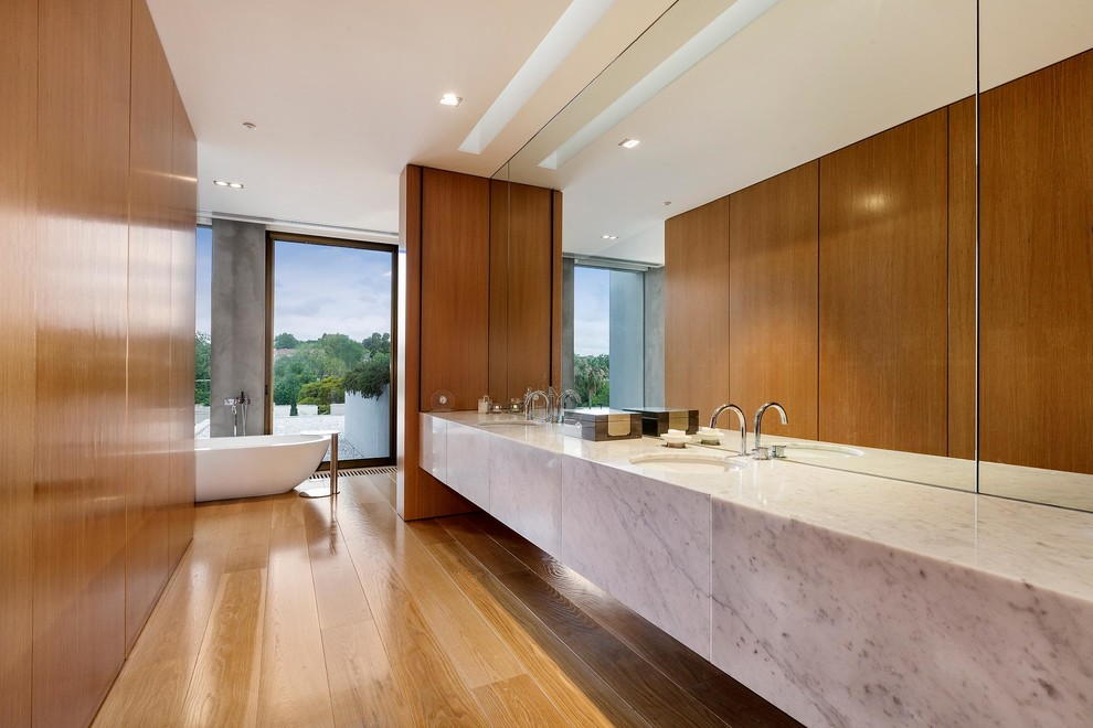 Inspiration for a modern master medium tone wood floor freestanding bathtub remodel in Melbourne with an undermount sink, flat-panel cabinets, marble countertops, brown walls and medium tone wood cabinets