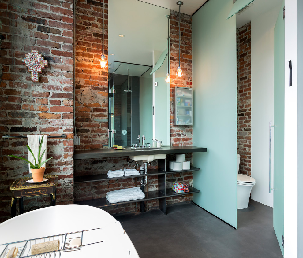 Urban concrete floor freestanding bathtub photo in Seattle with an undermount sink, open cabinets and a one-piece toilet