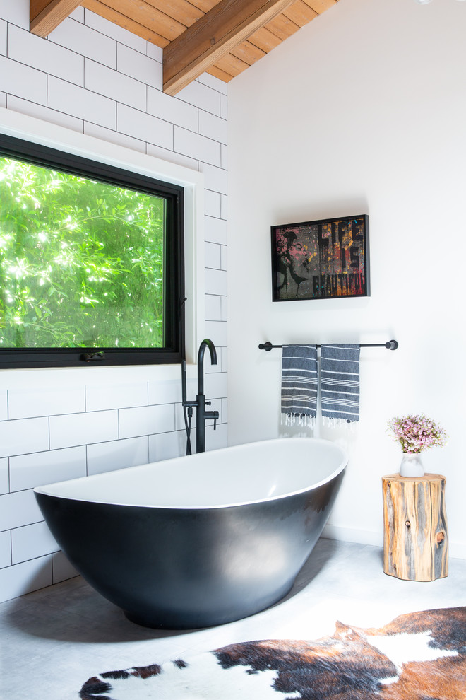 Inspiration for a transitional master white tile and subway tile concrete floor and gray floor freestanding bathtub remodel in Los Angeles with white walls