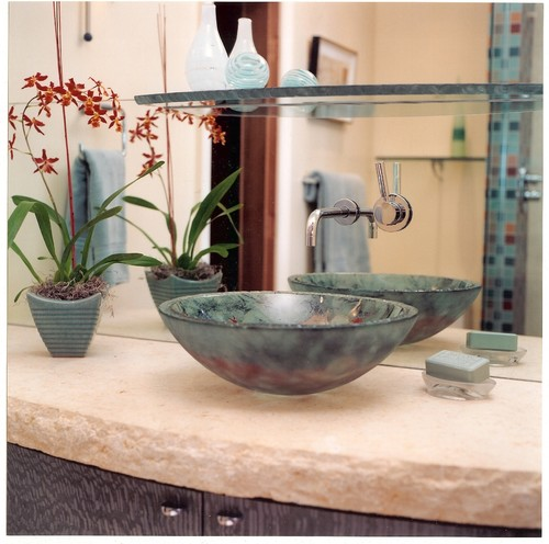 Vessel sink flanked by a potted plant and a bath soap