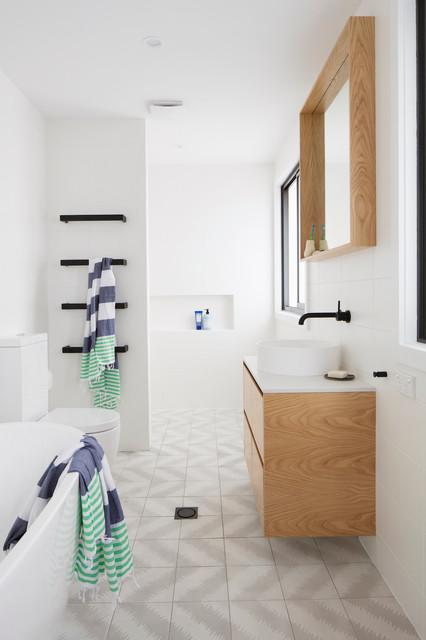 Foto di una stanza da bagno padronale minimal con ante lisce, ante in legno chiaro, vasca freestanding, doccia a filo pavimento, WC a due pezzi, piastrelle grigie, pareti bianche, pavimento con cementine, lavabo a bacinella e doccia aperta