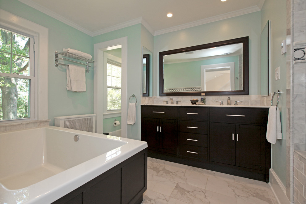 Example of a trendy gray tile drop-in bathtub design in Newark with shaker cabinets and dark wood cabinets