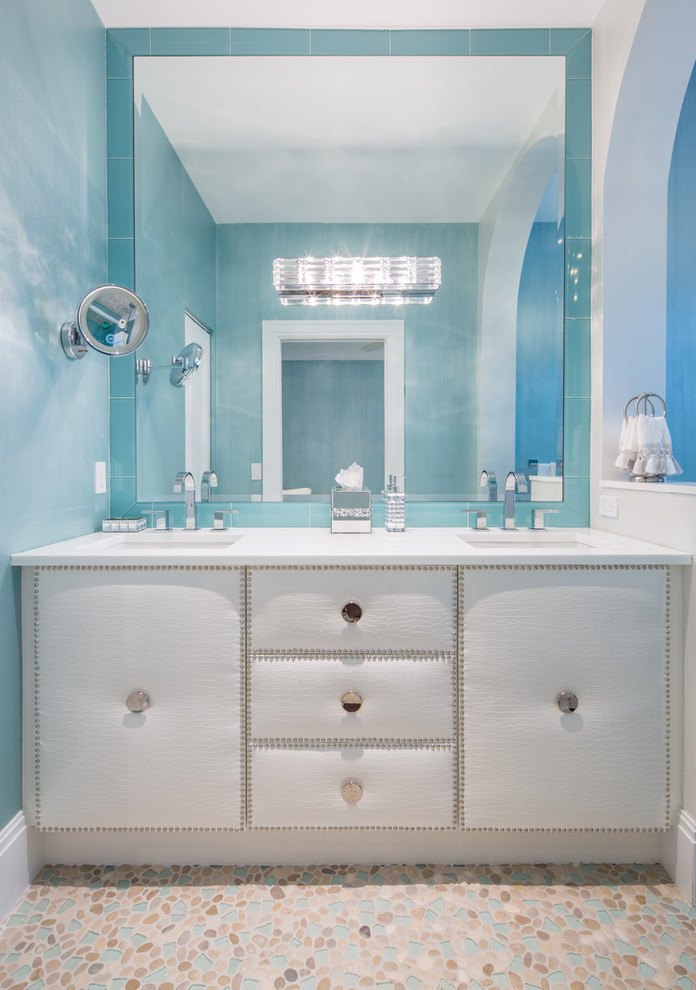 Mid-sized trendy kids' white tile and glass tile pebble tile floor alcove shower photo in Miami with an undermount sink, furniture-like cabinets, quartz countertops, a one-piece toilet, blue walls and white cabinets