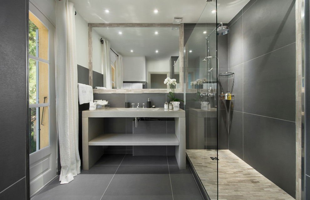 Corner shower - transitional gray tile corner shower idea in London with an integrated sink