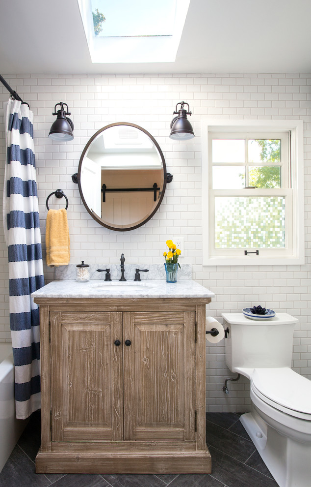 Beach style white tile and subway tile gray floor shower curtain photo in Seattle with raised-panel cabinets, medium tone wood cabinets, a one-piece toilet, white walls, an undermount sink and gray countertops