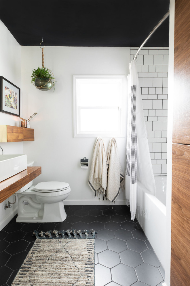 Trendy white tile black floor alcove bathtub photo in Sacramento with white walls, a vessel sink, wood countertops and brown countertops