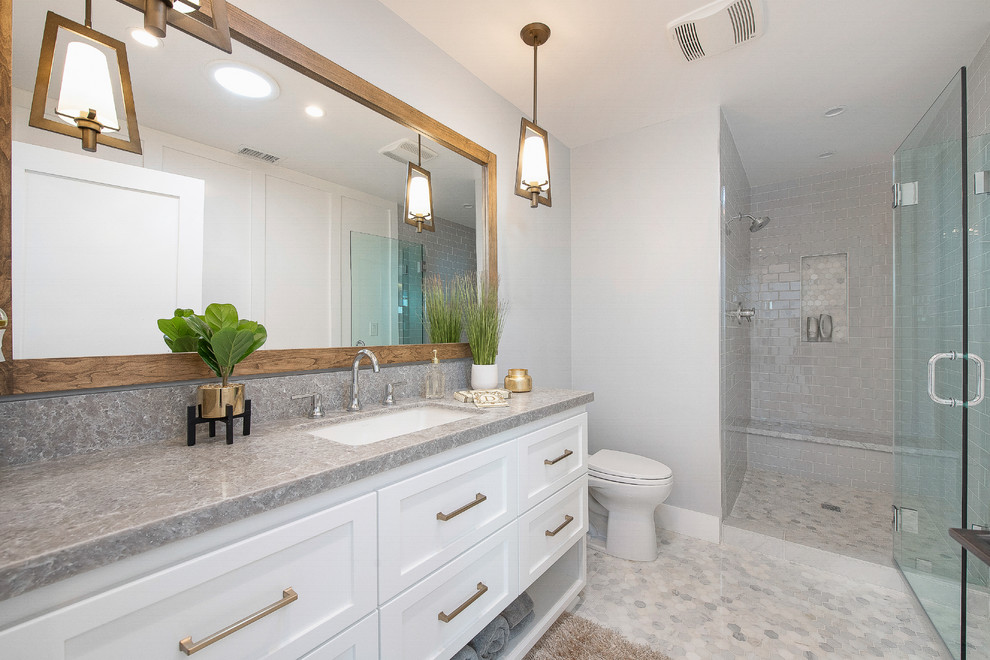 Example of a transitional master gray floor alcove shower design in Orange County with shaker cabinets, white cabinets, a two-piece toilet, white walls, an undermount sink, a hinged shower door and gray countertops