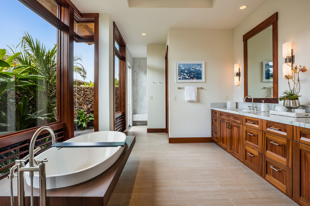 Inspiration for a tropical porcelain tile and beige floor freestanding bathtub remodel in Hawaii with shaker cabinets, medium tone wood cabinets, beige walls, an undermount sink and quartzite countertops
