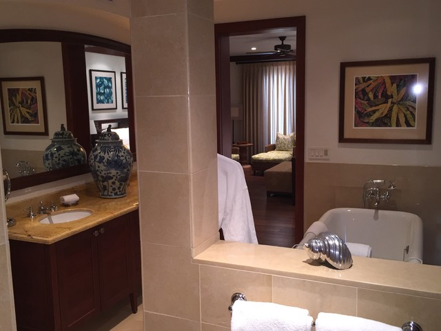 Inspiration for a large timeless master beige tile and stone tile limestone floor bathroom remodel in Hawaii with an undermount sink, recessed-panel cabinets, dark wood cabinets, marble countertops, a two-piece toilet and white walls