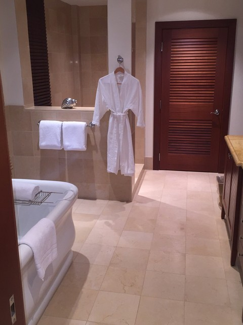 Large island style master beige tile and stone tile pebble tile floor bathroom photo in Hawaii with an undermount sink, recessed-panel cabinets, dark wood cabinets, marble countertops, a two-piece toilet and white walls