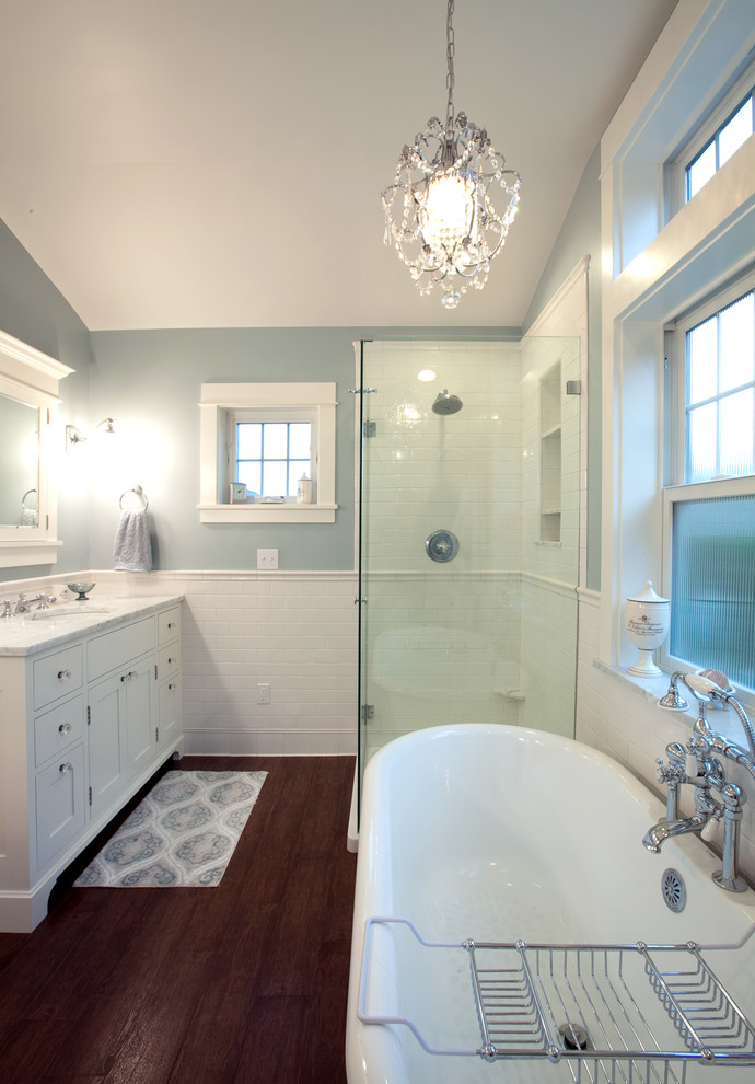 Elegant white tile and subway tile bathroom photo in Seattle with an undermount sink and white cabinets