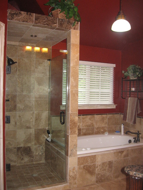 walk in shower with frameless shower door and travertine tile