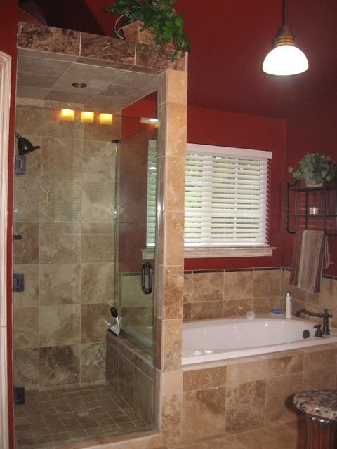 Walk in shower with frameless shower door, and travertine tile