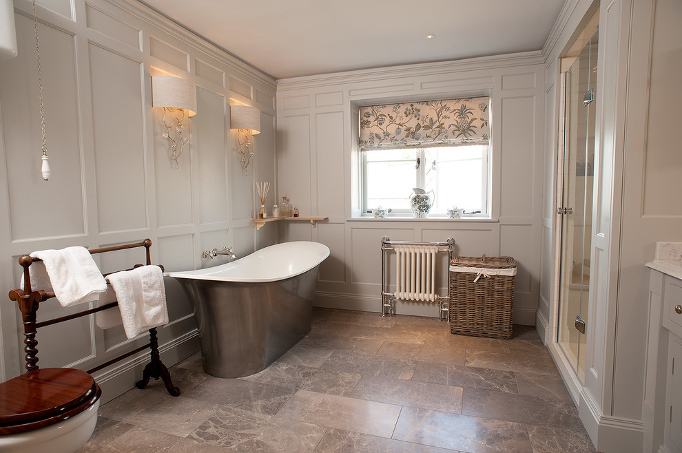 Freestanding bathtub - mid-sized traditional stone tile freestanding bathtub idea in Gloucestershire with a two-piece toilet and gray walls