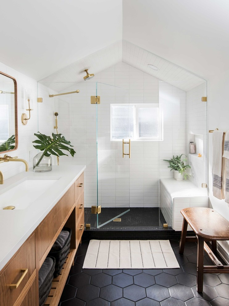 Inspiration for a transitional white tile black floor alcove shower remodel in Portland with flat-panel cabinets, medium tone wood cabinets, white walls, an undermount sink and white countertops