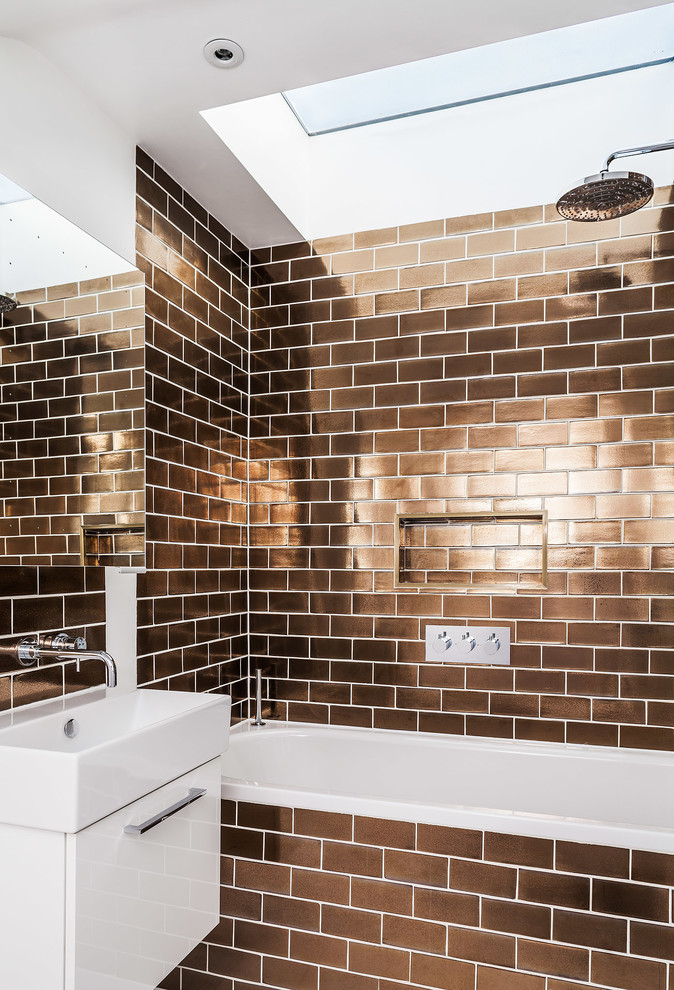 Example of a trendy brown tile and subway tile bathroom design in London with flat-panel cabinets, white cabinets and a console sink