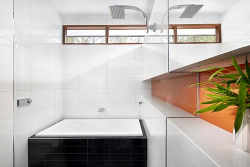 Orange backsplash: Is it glass over painted drywall? Acrylic panel?