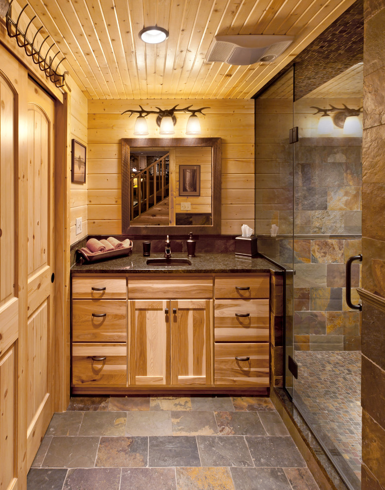 Example of a mountain style slate tile slate floor alcove shower design in Milwaukee with an undermount sink, flat-panel cabinets and medium tone wood cabinets