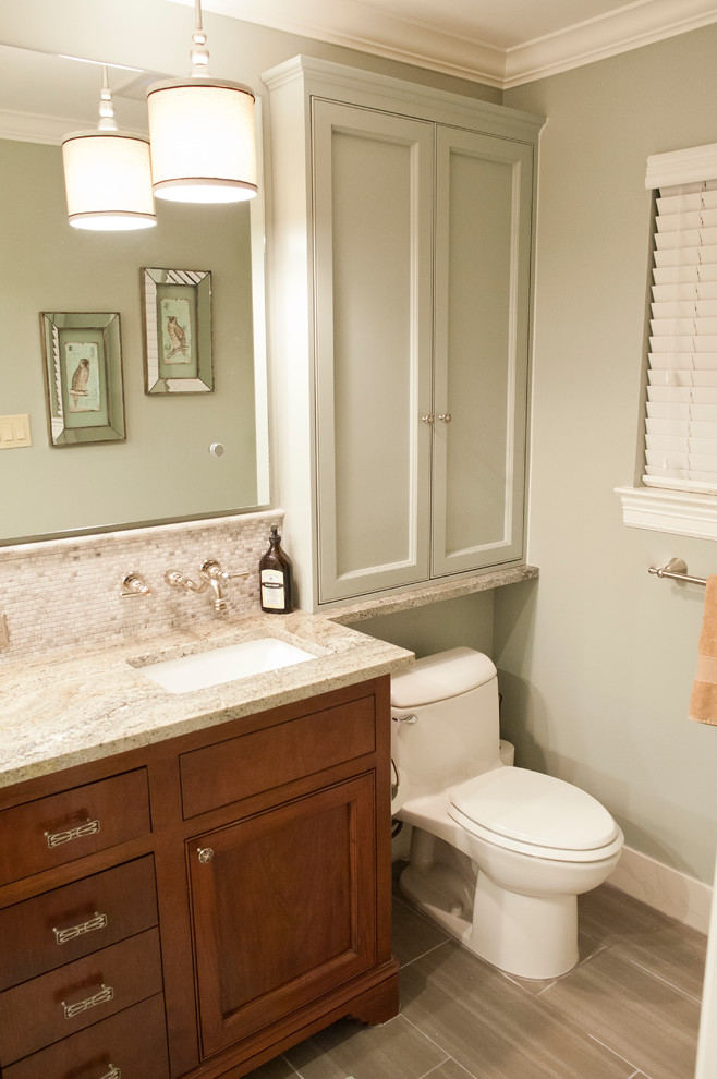 Example of a small transitional gray tile and porcelain tile porcelain tile bathroom design in Houston with an undermount sink, recessed-panel cabinets, dark wood cabinets, granite countertops, a one-piece toilet and green walls