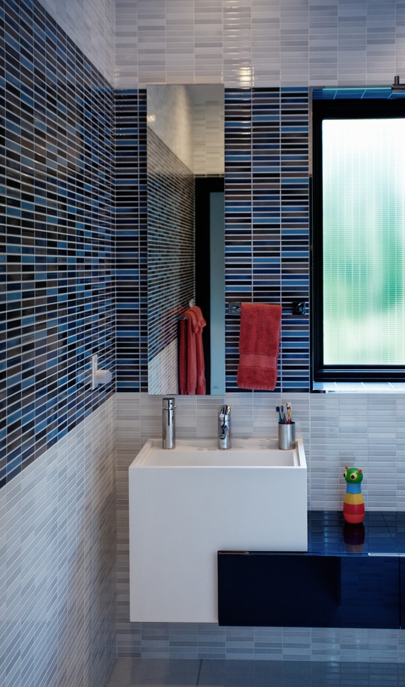 Bathroom - contemporary kids' blue tile and matchstick tile bathroom idea in New York with a wall-mount sink