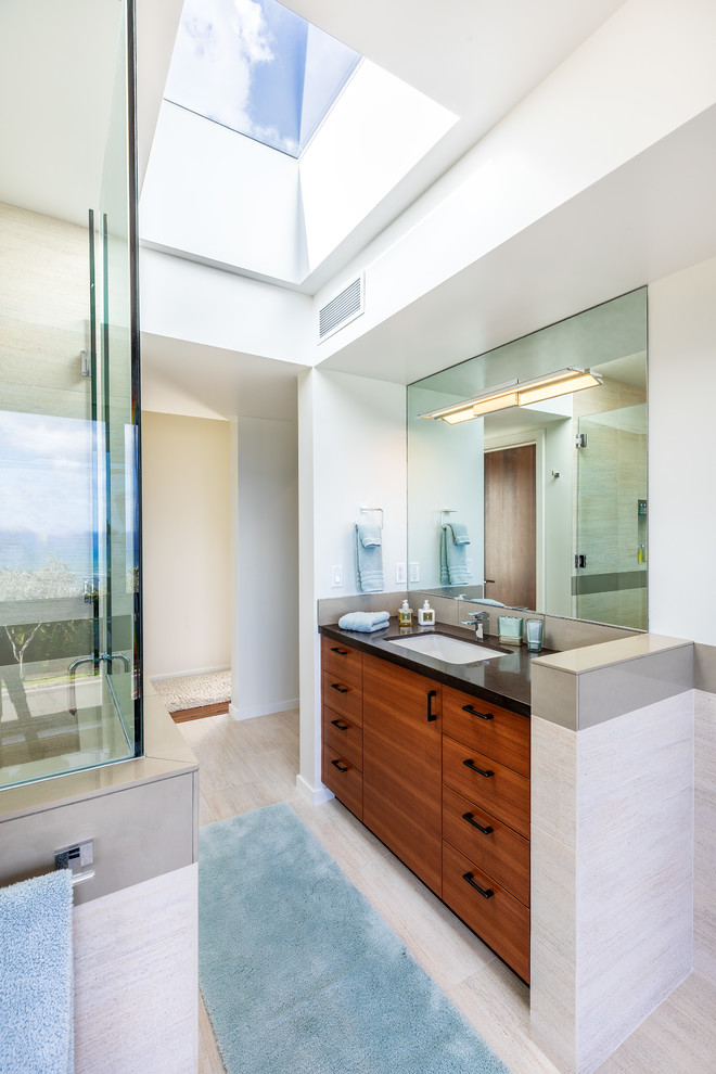 Large minimalist master beige tile and porcelain tile porcelain tile and beige floor alcove shower photo in Hawaii with flat-panel cabinets, medium tone wood cabinets, an undermount sink, granite countertops and a hinged shower door