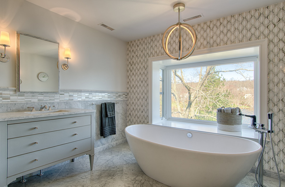 Freestanding bathtub - mid-sized transitional master mosaic tile marble floor freestanding bathtub idea in New York with furniture-like cabinets, gray cabinets, an undermount sink and gray walls