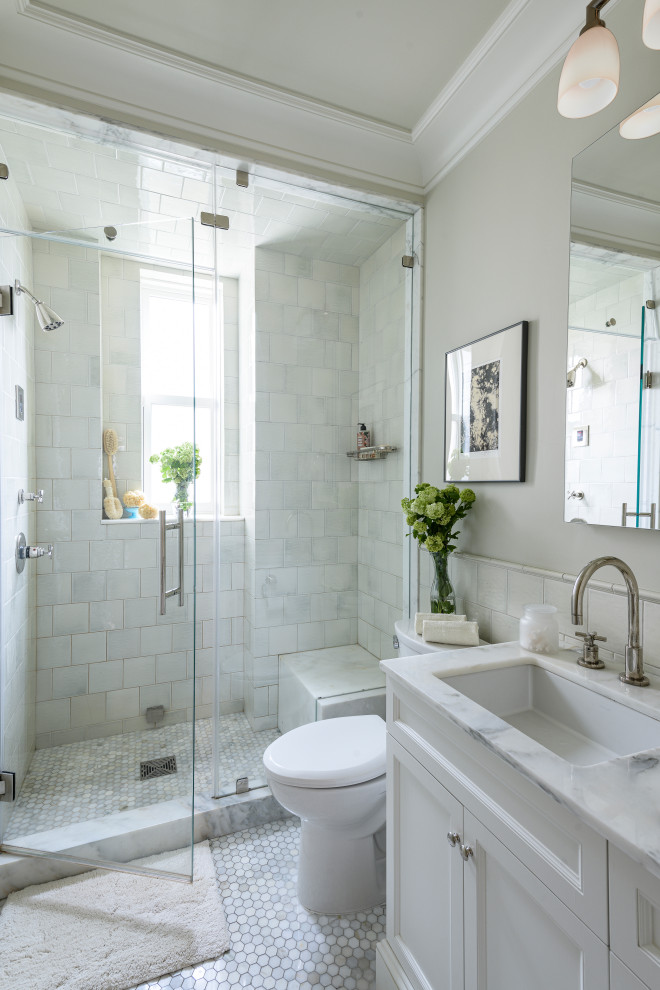 Alcove shower - mid-sized traditional master white tile and subway tile marble floor and gray floor alcove shower idea in New York with recessed-panel cabinets, white cabinets, a two-piece toilet, beige walls, an undermount sink, marble countertops, a hinged shower door and white countertops