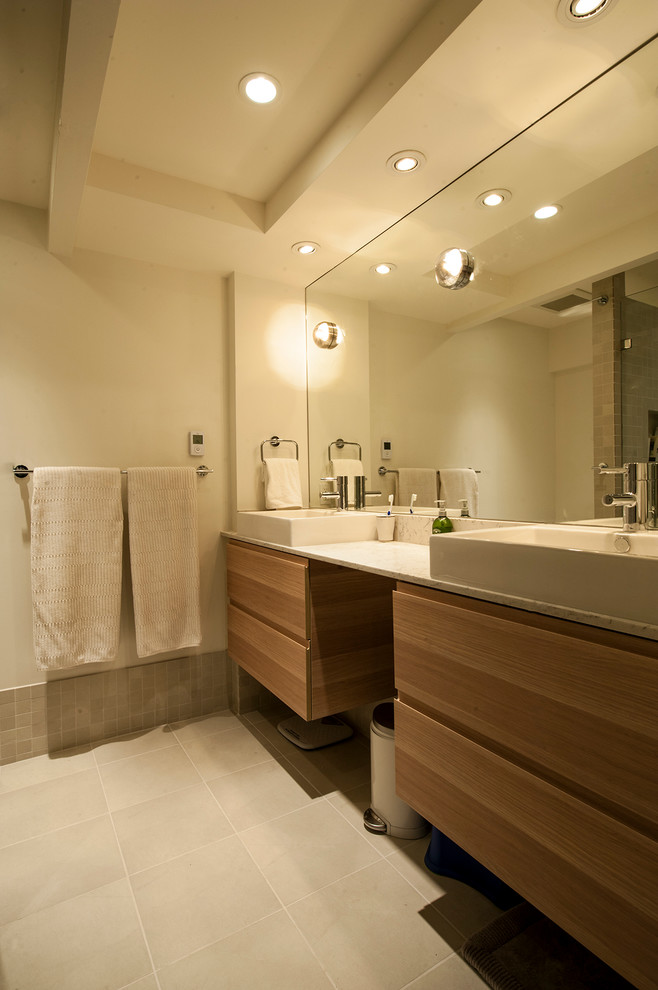 Mid-sized mid-century modern 3/4 white tile and ceramic tile ceramic tile walk-in shower photo in Vancouver with a vessel sink, flat-panel cabinets, medium tone wood cabinets, quartz countertops, a two-piece toilet and white walls