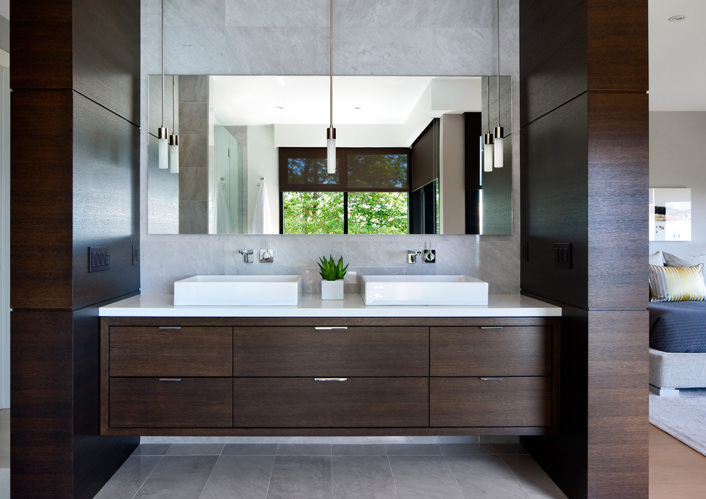 Trendy gray tile bathroom photo in Vancouver with a vessel sink, flat-panel cabinets and dark wood cabinets
