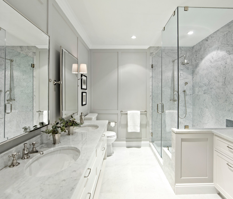 Inspiration for a large transitional master white tile and stone tile corner shower remodel in New York with shaker cabinets, white cabinets, gray walls, marble countertops and a hinged shower door