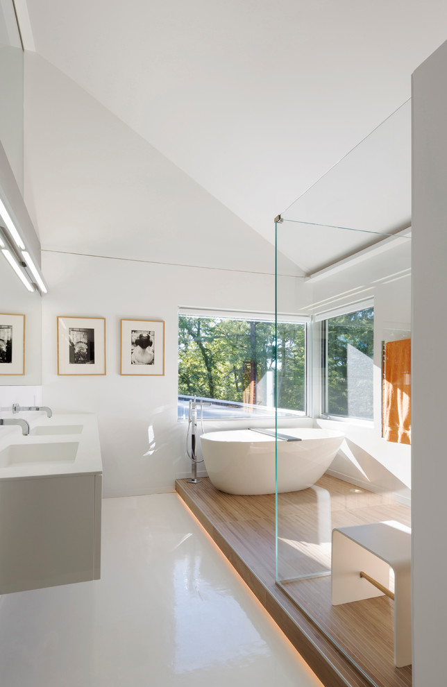 Example of a large trendy master white tile white floor bathroom design in San Francisco with an integrated sink, white cabinets, white walls, flat-panel cabinets, a hinged shower door and a floating vanity