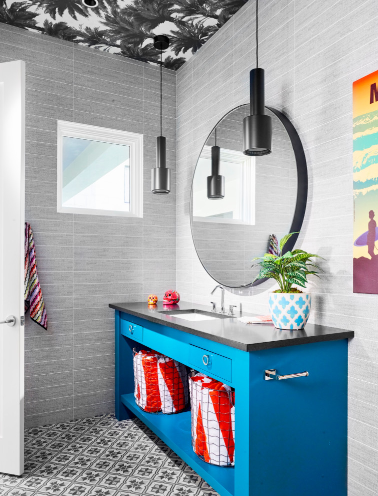 Mid-sized beach style 3/4 gray tile ceramic tile, gray floor and single-sink bathroom photo in Austin with open cabinets, blue cabinets, gray walls, a drop-in sink, black countertops and a built-in vanity
