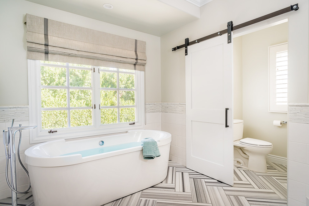 Freestanding bathtub - large transitional master white tile marble floor freestanding bathtub idea in Los Angeles with a two-piece toilet and beige walls