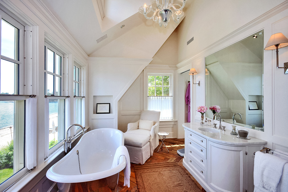 Elegant master medium tone wood floor freestanding bathtub photo in New York with an undermount sink, recessed-panel cabinets, beige walls and white cabinets
