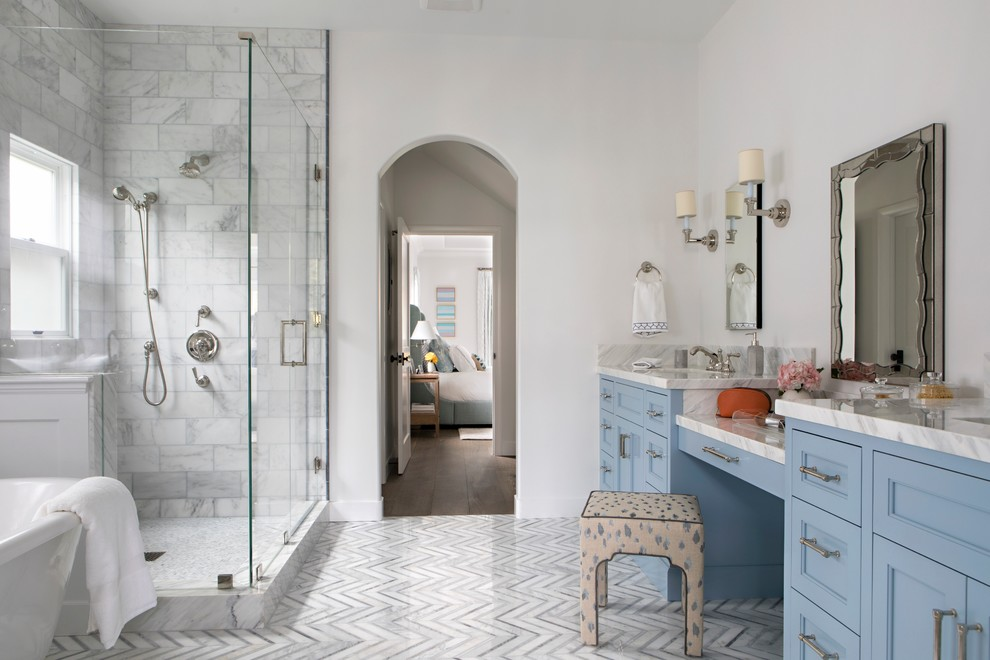 Inspiration for a large transitional master marble tile and white tile marble floor and gray floor bathroom remodel in Los Angeles with blue cabinets, a one-piece toilet, white walls, an undermount sink, marble countertops, a hinged shower door, recessed-panel cabinets and white countertops