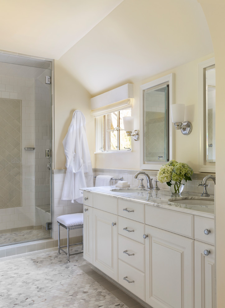 Elegant white tile marble floor and white floor alcove shower photo in Los Angeles with raised-panel cabinets, white cabinets, yellow walls, an undermount sink, marble countertops and a hinged shower door