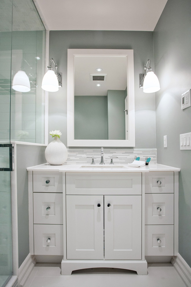 Example of a small transitional white tile and porcelain tile porcelain floor bathroom design in Toronto with an undermount sink, shaker cabinets, white cabinets, marble countertops, a two-piece toilet and blue walls