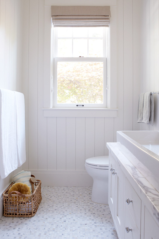 White bathroom with tile floor and lots of light