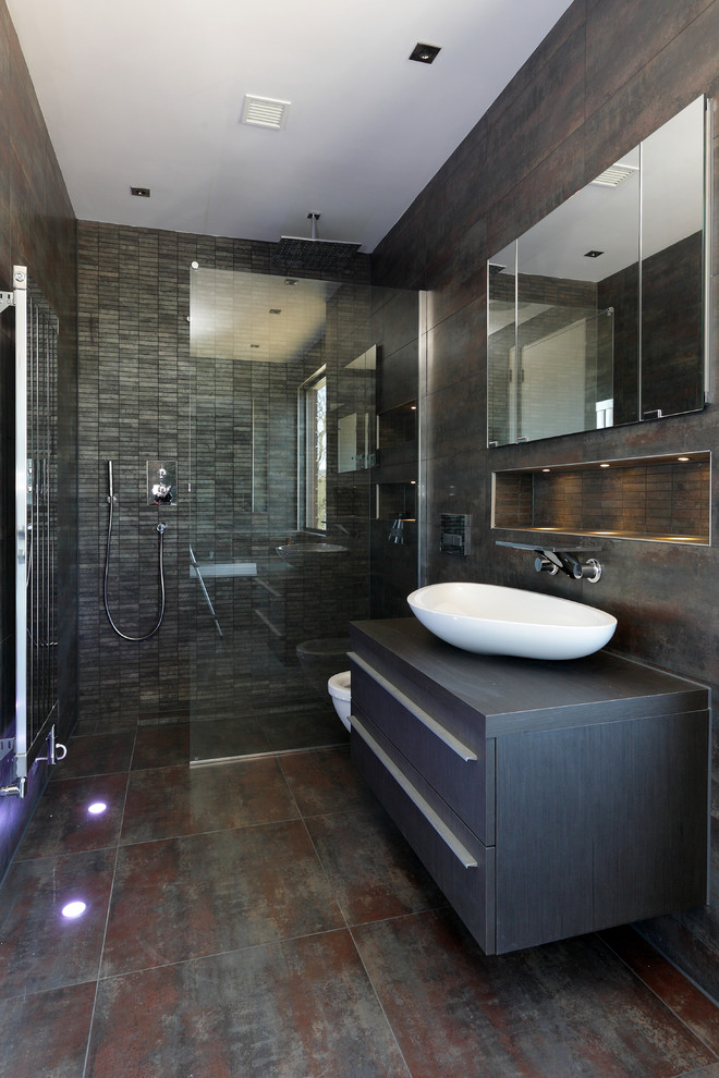 Contemporary bathroom in London with a vessel sink, flat-panel cabinets, dark wood cabinets, wood benchtops, a corner shower and grey walls.